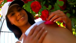 Teen beauty walking through the whole of with roses and she is touching her very well body